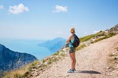 Vrouwentoerist die op Garda-Meer van Monte Altissimo-berg in Malcesine kijken stock afbeelding