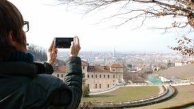 Vrouwentoerist die slimme telefoon met behulp van, die beeld nemen aan stedelijk panorama de reisbestemming in van Turijn, Turijn stock video