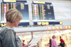 Vrouwentoerist die tijdschema in luchthaven bekijken stock fotografie