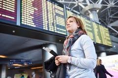 Vrouwentoerist die zich bij luchthaven op achtergrond van vertrek bevinden stock afbeeldingen