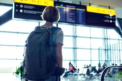 Vrouwentoerist in luchthaventerminal die op vlucht en het kijken wachten stock foto's