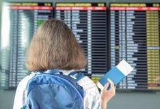 Vrouwentoerist in luchthaventerminal die op vlucht wachten en tijdschema met paspoort en kaartje bekijken royalty-vrije stock foto's