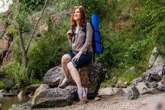 Vrouwentoerist met een rugzakgang in een stijging tegen een achtergrond van mooi berglandschap langs een bergrivier stock foto