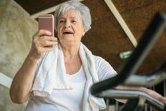 Vrouwentraining in gymnastiek Vrouw die slimme telefoon op elli met behulp van Royalty-vrije Stock Afbeeldingen