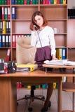 Vrouwentribune dichtbij bureau en het spreken op telefoon stock foto