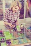 Vrouwenverkoper die zich bij teller met diverse schaar in het naaien bevinden Stock Foto