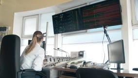 Vrouwenverzender van de spoorweg op het werk De monitors van het treintijdschema, treincontrolebord stock footage