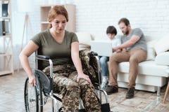 Vrouwenveteraan in rolstoel van leger is teruggekeerd dat Een vrouw in een rolstoel is in pijn Zij ` s in militaire eenvormig royalty-vrije stock foto