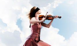 Vrouwenviolist in rode kledings speelmelodie tegen bewolkte hemel royalty-vrije stock foto's
