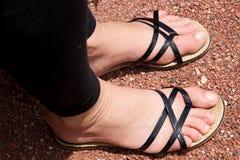 Vrouwenvoeten in sandals Stock Fotografie