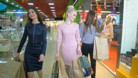 Vrouwenvrienden die over het winkelen verkoop worden opgewekt, die in wandelgalerij lopen 4K stock video