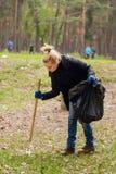 Vrouwenvrijwilliger die huisvuil in park verzamelen Royalty-vrije Stock Foto's