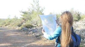 Vrouwenwandelaar die een kaart naast stroom lezen stock video