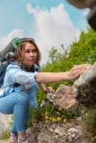 Vrouwenwandelaar die op een rotsachtige bergweg beklimmen, die bij de stenen clutching Bomen en hemel op de achtergrond royalty-vrije stock foto