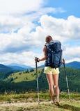 Vrouwenwandelaar die op grasrijke heuvel wandelen, die rugzak dragen, die trekkingsstokken in de bergen gebruiken royalty-vrije stock fotografie