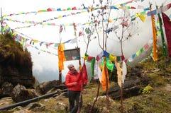 Vrouwenwandelaar en gebedwiel in de Bergen van Himalayagebergte, Nepal stock fotografie