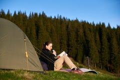 Vrouwenwandelaar met boek dichtbij de tent in de avond Stock Fotografie