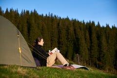 Vrouwenwandelaar met boek dichtbij de tent in de avond Stock Foto's