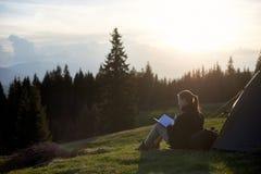Vrouwenwandelaar met boek dichtbij de tent in de avond Royalty-vrije Stock Foto's
