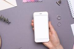 Vrouwenwerkdag met in hand telefoon en notitieboekje op grijze achtergrond royalty-vrije stock foto's