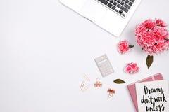 Vrouwenwerkruimte met laptop, met de hand geschreven citaatnotitieboekje, roze ca Stock Foto's