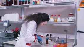 Vrouwenwetenschapper die in een laboratorium werken stock footage