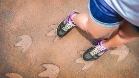 Vrouwenzegel haar schoen op dinosaurusvoetafdrukken Royalty-vrije Stock Foto