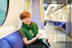 Vrouwenzitting aan de gang en bestuderend routekaart Kaukasische roodharigetoerist in glazen in wagen van metro reiziger in de me royalty-vrije stock foto