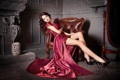 Vrouwenzitting als voorzitter in lang Bordeaux, purpere kleding luxe royalty-vrije stock afbeeldingen