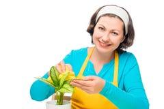 Vrouwenzitting bij de lijst en de oneffenheden de bloembladeren Stock Fotografie