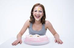 vrouwenzitting bij de lijst met cake bij haar gezicht stock fotografie