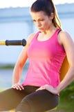 Vrouwenzitting bij gewichtenmachine de ademhaling stock fotografie