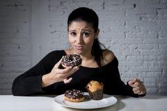 Vrouwenzitting bij lijst die schuldig het vergeten dieet voelen die schotelhoogtepunt van troep suikerachtig ongezond voedsel ete stock foto
