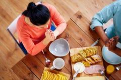 Vrouwenzitting bij lijst en het bidden vóór maaltijd Stock Afbeelding
