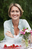 Vrouwenzitting bij Lijst in Tuin Royalty-vrije Stock Fotografie