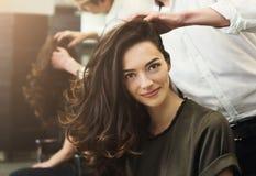 Vrouwenzitting bij schoonheidssalon, die kapsel maken royalty-vrije stock foto