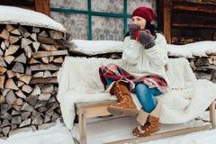 Vrouwenzitting buiten een plattelandshuisje die van een sneeuwdag op haar genieten  Stock Foto