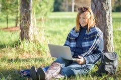 Vrouwenzitting buiten het werken aan laptop Royalty-vrije Stock Afbeeldingen