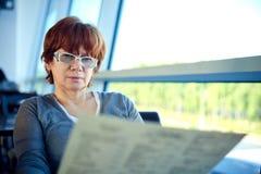 Vrouwenzitting in de luchthavenkoffie en wachten voor vertrek stock fotografie