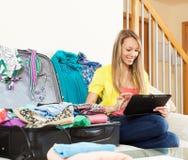 Vrouwenzitting dichtbij koffer terwijl het gebruiken van digitale tablet Stock Afbeelding