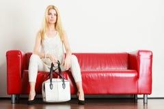 Vrouwenzitting die op bank witte zak houden Stock Fotografie