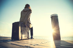 Vrouwenzitting die op haar koffer op de zonsondergang wachten Royalty-vrije Stock Afbeeldingen