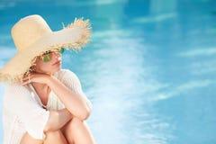 Vrouwenzitting door de poolkant en het glimlachen over haar s royalty-vrije stock foto