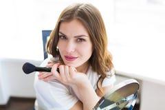 Vrouwenzitting door de spiegel Stock Foto's