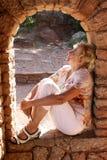 Vrouwenzitting in een boog van oude ruïnes Stock Afbeeldingen
