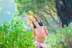 Vrouwenzitting in een bos die haar haar met bomen op de achtergrond flicking royalty-vrije stock afbeeldingen