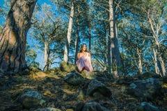 Vrouwenzitting in een bos met bomen op de achtergrond royalty-vrije stock fotografie