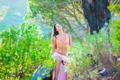 Vrouwenzitting in een bos met bomen op de achtergrond stock foto's