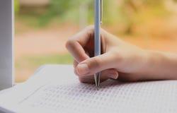 Vrouwenzitting en holding een blauw potlood voor het doen van een examen stock afbeelding