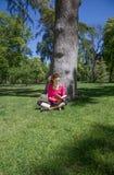Vrouwenzitting in gras in het boek van de parklezing Royalty-vrije Stock Foto
